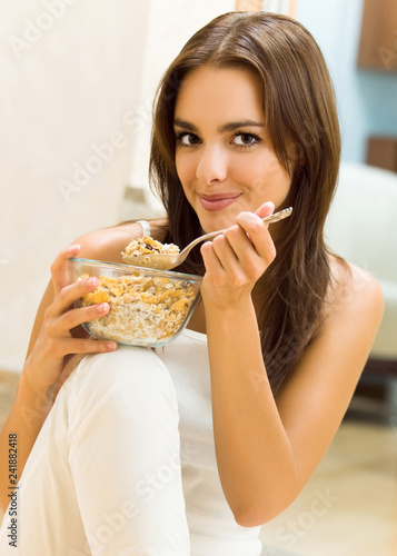 Fotografie, Obraz  Young woman eating cereal muslin (flakes)