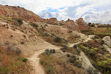 A Winding Mountain Trail Passes Between Huge And Old Stones In The Cappadocian Red Valley.