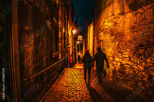 Couple walking through a narrow street in Edinburgh at the Royal Mile night shot Edinburgh at Night Scotland travel concept
