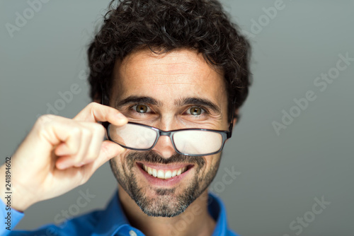 Portrait of a handsome man holding eyeglasses