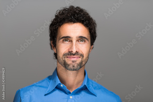 Closeup portrait of a happy young man smiling on gray background