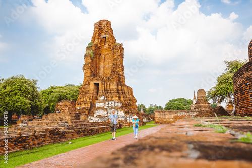Foto  Group of two tourists walking among ancient ruins at Wat Mahathat in Ayutthaya h