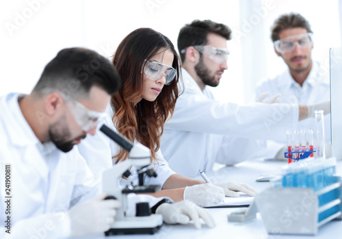 Photo  scientist looking in a microscope sitting in the lab.