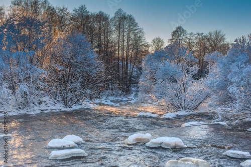 Fotografía  rough river in winter with snow-covered trees and steam