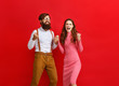 canvas print picture - young happy couple won emotionally celebrating win on colored red background.