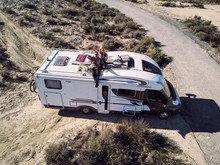 Couple Sitting At Camper Car Roof And Waving Hands
