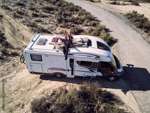 Photo  Couple sitting at camper car roof and waving hands