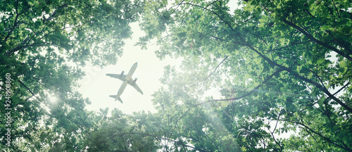 Photo sur Aluminium Avion à Moteur Eco-friendly air transport concept. The plane flies in the sky against the background of green trees. Environmental pollution. Harmful emissions