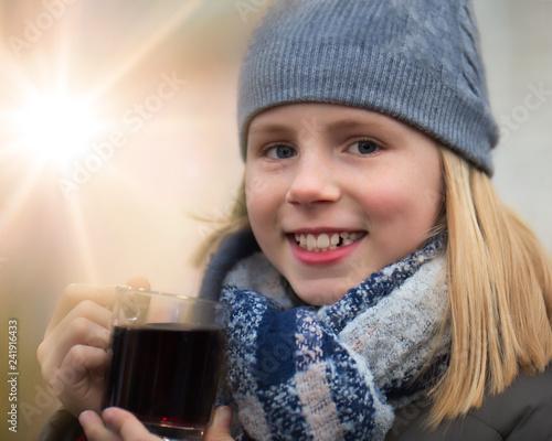 Mädchen hält glücklich einen Kinderpunsch als warmes Getränk auf einem Weihnachtsmarkt