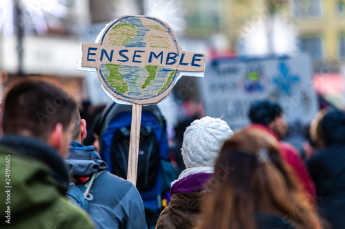 Activists marching for the environment. French sign seen in an ecological protest saying together, on an earth depiction