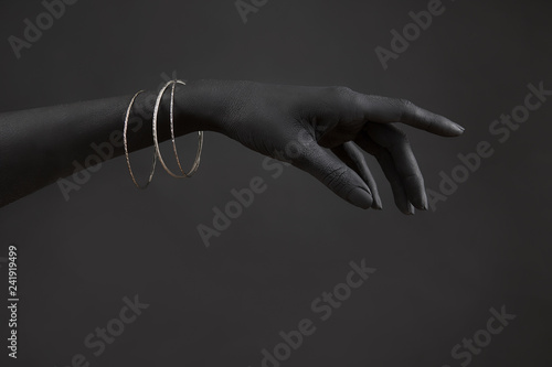 Black woman's hand with Silver jewelry. Oriental Bracelets on a black painted hand. Silver Jewelry