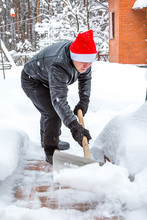 A Man Cleans Steps From Snow. In A Red Hat Of Santa Claus And A Leather Black Jacket. In Felt Boots. Clearing Snow From The Backyard After A Snowfall.