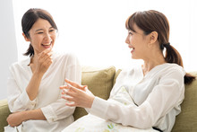 Two Young Asian Women Relaxing In Living Room