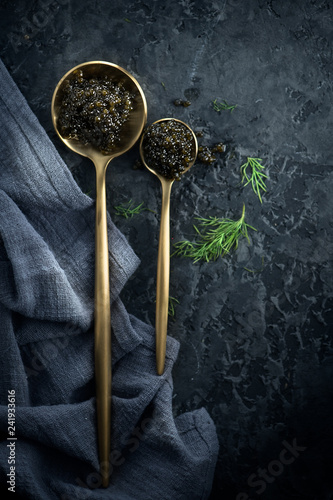 Black caviar in spoons on dark background. Natural sturgeon black caviar closeup. Delicatessen. Top view, flatlay