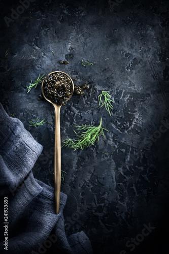 Black caviar in a spoon on dark background. Natural sturgeon black caviar closeup. Delicatessen. Top view, flatlay