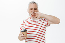 Waist-up Shot Of Sleepy And Tired Grandfather With Grey Hair Yawning With Closed Eyes Holding Paper Cup Of Coffee Standing Sleepy With Closed Eyes In Morning Feeling Tired Waking Up Early