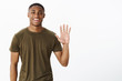 Friendly attractive nice african american male friend raising palm to wave smiling broadly saying hello, greeting friends in cafe welcoming or inviting people to party, posing over gray background