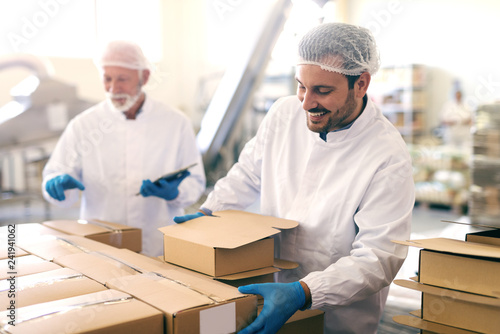 Young Caucasian man relocating boxes with cookies in food factory. In background his boss counting boxes and holding tablet.