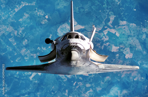 Spaceship on the flight. Space shuttle close-up. Flying rocket. View of the planet Earth  from outer space. Some elements of this image are furnished by NASA