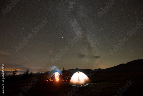In de dag Kamperen Night camping under beautiful starry sky. Group of four people, men and woman resting by burning campfire at tourist tents under dark sky with bright sparkling stars and Milky Way constellation.