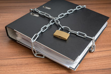 Confidential Files And Documents In Binder Locked With Padlock And Chain.