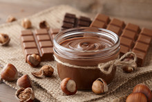Chocolate Spread Or Nougat Cream With Hazelnuts In Glass Jar On Wooden Background