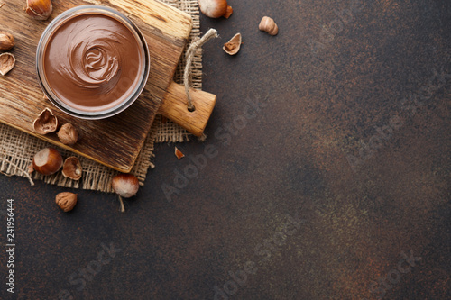 Valokuva  Chocolate spread or nougat cream with hazelnuts in glass jar on brown textured c