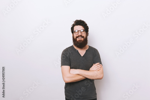 Happy smiling bearded man with crossed hands standing over white wall Canvas Print
