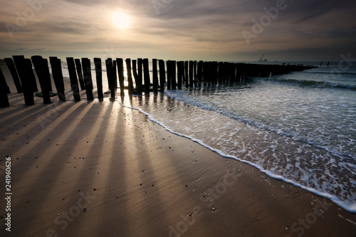 Poster Cote sunshine over old wooden breakwater on North sea coast