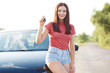 Pretty brunette young European woman shows car key, rejoices new purchase, poses near new automobile, dressed in casual t shirt and denim shorts, poses outside. Female seller advertises her vehicle