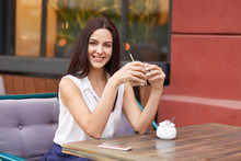 Pleased Brunette Lady Holds Fresh Cocktail, Sits At Wooden Table In Cozy Outdoor Cafeteria, Uses Modern Mobile Phone, Spends Spare Time With Friends, Has Day Off. People, Leisure, Lifestyle Concept