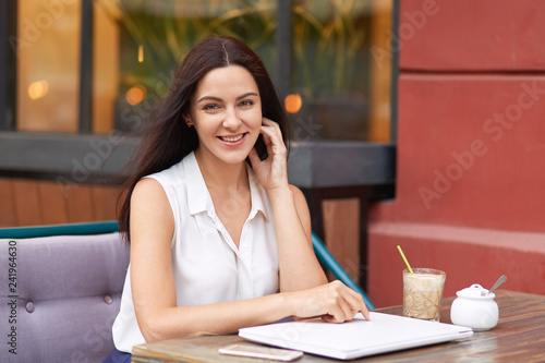 Fotografie, Obraz  Positive dark haired woman in white outfit, surrounded with modern gadgets, sits at coffee shop, smiles gently at camera, being in good mood, waits for order, going to gave lunch after work