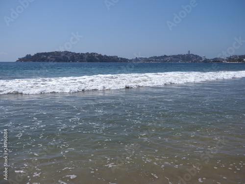 Fotografija  Scenery of calm beach at bay of ACAPULCO city in Mexico and white waves of Pacif