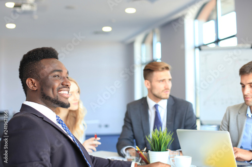 Photographie  Smiling confident African businessman in a meeting with a colleagues seated at a conference table in the office