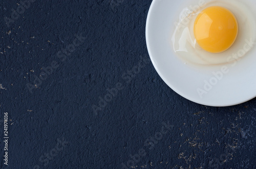 Chicken raw egg without a shell in a white plate on a blue background.
