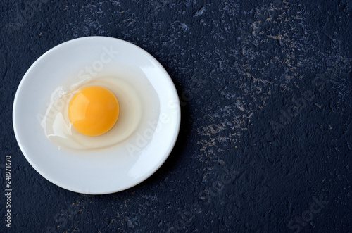 Raw egg guinea fowl in a white plate on a blue background