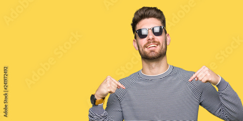 Fotografie, Obraz  Young handsome man wearing sunglasses looking confident with smile on face, pointing oneself with fingers proud and happy