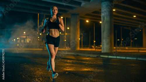 Beautiful Fitness Girl in Black Athletic Top and Shorts is Jogging on the Street. She is Doing a Workout in an Evening Wet Urban Environment Under a Bridge.