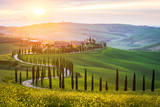 Typowy krajobraz Toskanii - kręta droga wysadzana cyprysami wśród zielonych łąk i pól. Zachód słońca we Włoszech.