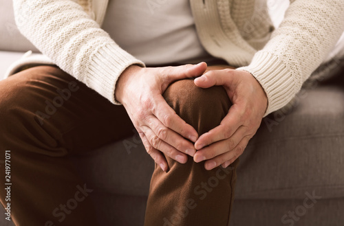 Foto  Mature man suffering from knee pain on sofa