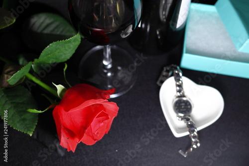Fotografia  赤い薔薇の花と腕時計と赤ワインのグラスとボトル(黒背景)