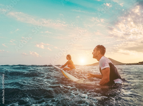 Fit couple surfing at sunset Canvas Print