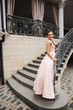 Elegant lady satnd on stairs in front of restaurant