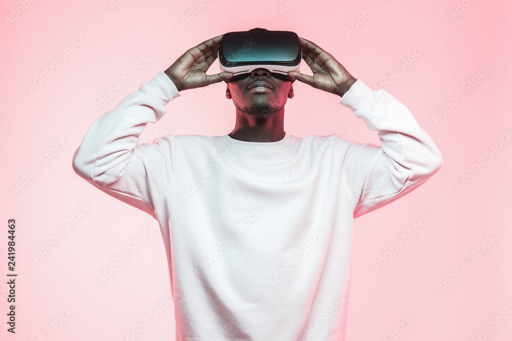 Fototapeta Young african man holding virtual reality goggles with both hands, isolated on pink background