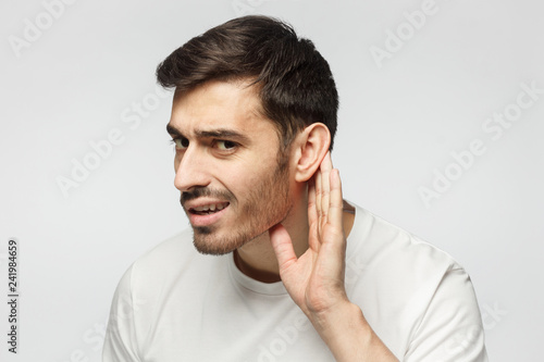 Fotografia Man isolated on gray background pressing hand to ear trying to hear something be