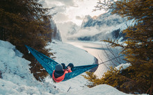Young Man By The Lake Hanging On Hammock Relaxing In The Morning And Stretching Arms Outstretched . People Relaxation Travel Concept. Famous Gosau Lake In Salzkammergut With The Dachstein In Winter.
