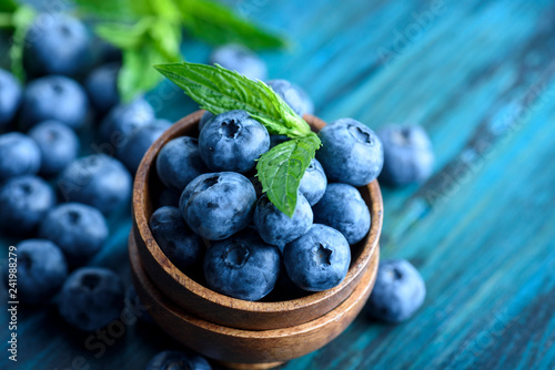 Leinwand Poster Bowl of fresh blueberries on blue rustic wooden table closeup.
