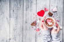Girl Hands Hold Little Heart Shaped Gift Box, Old Wooden Table With Hot Chocolate With Marshmallow Hearts And Tulip Flowers, Valentine Day Background Copy Space Top View, Hands In Picture Flatlay