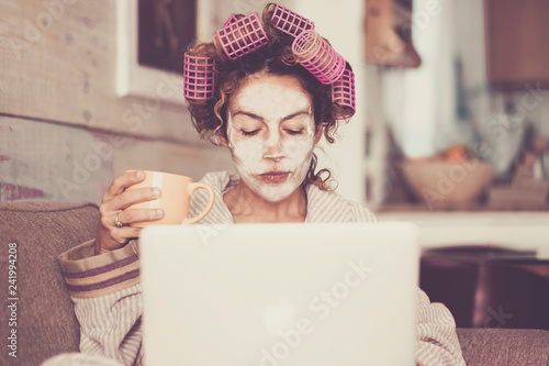 Photo Rare and funny portrait of beautiful woman with facial mask and curlers hair tak