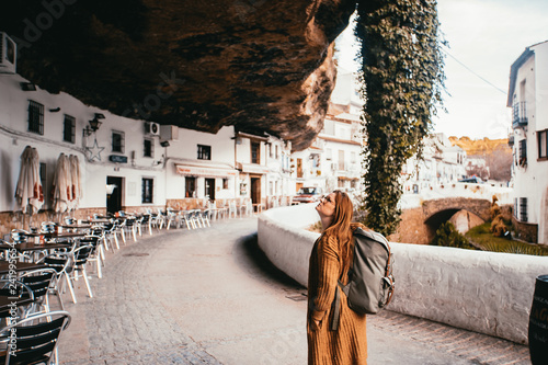 Young female tourist with a backpack is locking above in a small spain village that is build into a rock.